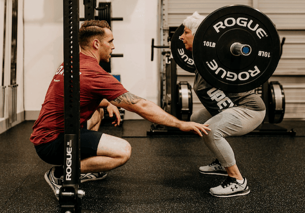 A fitness coach teaching a back squat